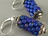 prayer wheel earrings in blue oil