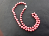 Beautiful coral necklace hand knotted onto silk with a sterling silver clasp .