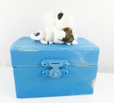 Clay white baby dragon on an old blue treasure chest